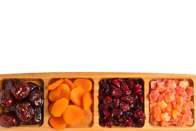 Mischung aus getrockneten früchten und nüssen. aprikose, rosine, cranberry, dattelfrucht. isoliert auf weißem hintergrund. platz für text oder design.