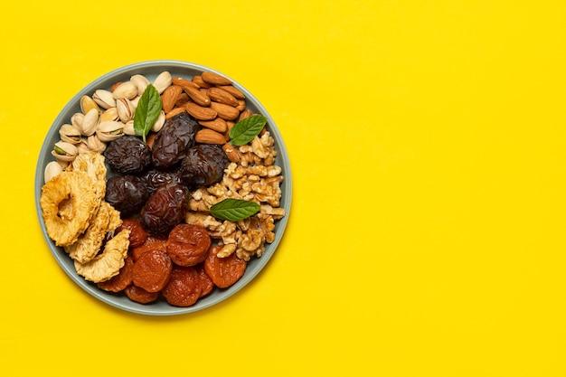 Mischung aus getrockneten früchten und nüssen auf einem teller auf gelbem grund mit kopierraum. sicht von oben. symbole des jüdischen feiertags von tu bishvat