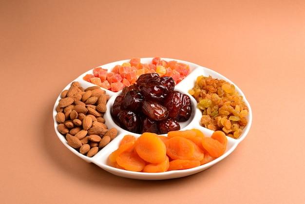 Mischung aus getrockneten früchten und nüssen auf einem weißen teller. aprikose, mandel, rosine, dattelfrucht. auf einer braunen oberfläche