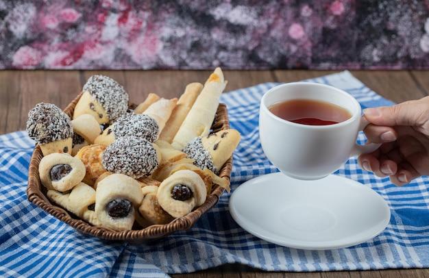 Mischung aus keksen auf einer platte, serviert mit einer tasse earl grey tee.