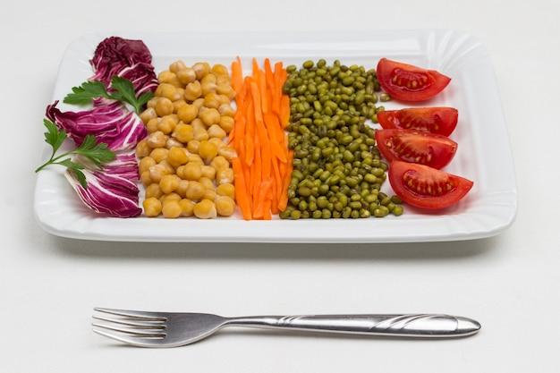 Mischung aus kichererbsen und mungobohnen, kohlblättern, karotten und tomaten. ausgewogene ernährung. flach liegen.