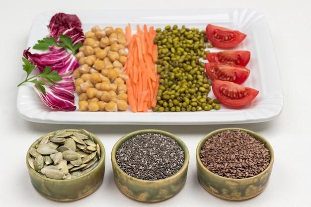 Mischung aus kichererbsen und mungobohnen, kohlblättern, karotten und tomaten. leinsamen, kürbiskerne, schwarze chia in kisten. ausgewogene ernährung.
