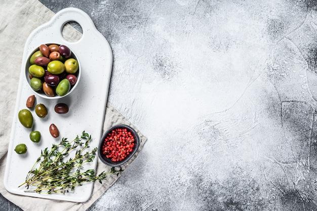 Mischung aus marinierten oliven mit knochen. grauer hintergrund. ansicht von oben. platz für text