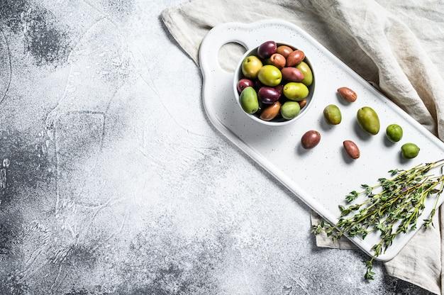 Mischung aus marinierten oliven und knochen. grauer hintergrund. draufsicht. platz für text