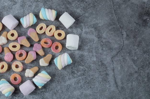 Mischung aus marshmallow und jellybeans auf dem marmortisch.