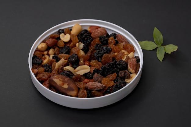 Mischung aus nüssen mit getrockneten früchten, erdnüssen, paranüssen, cashewnüssen, mandeln, schwarzen rosinen und weißen rosinen Premium Fotos