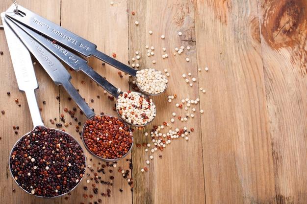 Mischung aus quinoakorn in metallmesslöffeln