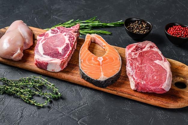 Mischung aus rohen fleischsteaks, lachs, rindfleisch, schweinefleisch und hühnchen
