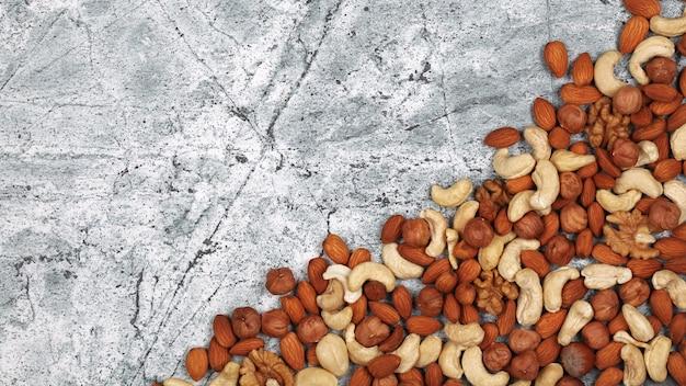 Mischung aus rohen nüssen auf grauem steinhintergrund. draufsicht mit kopienraum