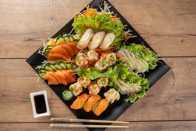 Mischung aus sushi und niguiris auf schwarzem teller