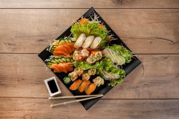 Mischung aus sushi und niguiris in schwarzer platte auf holztisch