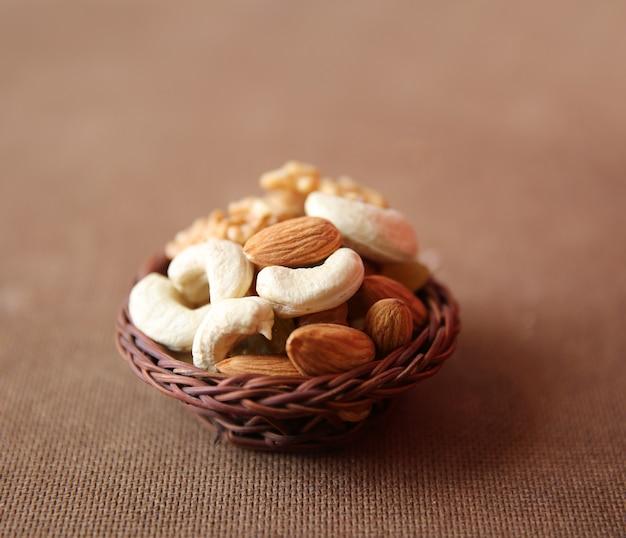 Mischung aus trockenen nüssen und früchten nahaufnahme mit holzkorb