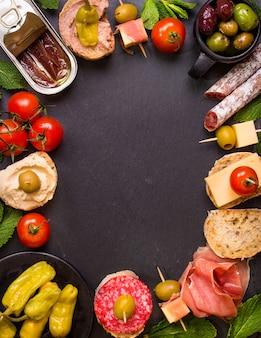 Mischung aus verschiedenen snacks und vorspeisen. spanische tapas auf einem schwarzen steinhintergrund.