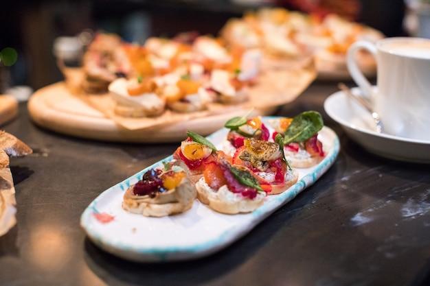 Mischung aus verschiedenen snacks und vorspeisen. spanische tapas auf einem schwarzen steinraum. bar. platz für text. feinkost, sandwiches, oliven, wurst, sardellen, käse, jamon, pfeffer, tomaten. draufsicht