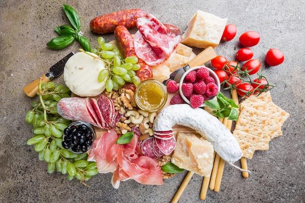 Mischung aus verschiedenen snacks und vorspeisen. spanische tapas oder italienischer wein auf einer holzplatte.