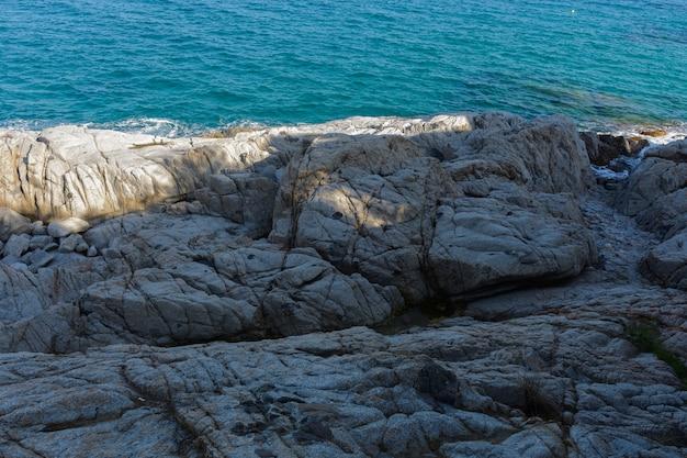 Mischung aus weißen erleuchteten felsen und blauen mittelmeer meeren in platja d'aro, spanien