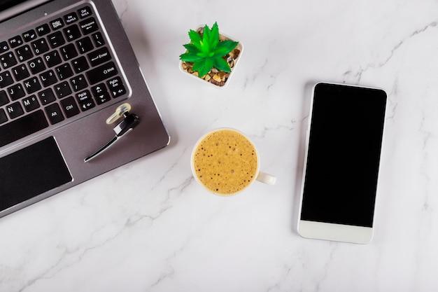 Mischung des büroartikels mit den intelligenten telefongeräten, die an einer laptop-computer in einem tasse kaffee auf einem drahtlosen kopfhörer arbeiten