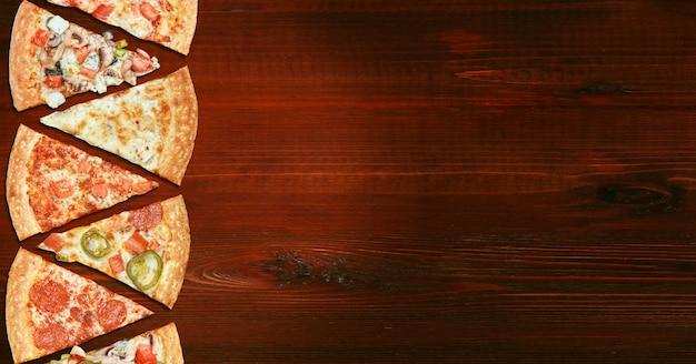 Mischung von acht verschiedenen pizzen auf einem holztischmenükonzept der wahl und der verschiedenartigkeit