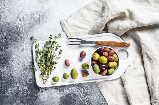 Mischung von bunten gesalzenen oliven in der grauen oberfläche