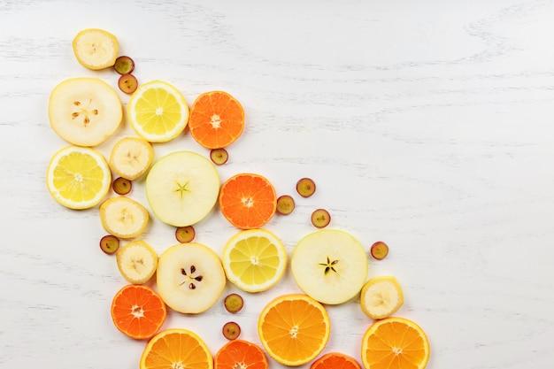 Mischung von farbigen früchten auf weißem hölzernem hintergrund - zusammensetzung des tropischen hintergrundes der gesunden ernährung und des lebensmittels