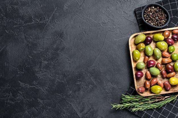 Mischung von farbigen in essig eingelegten oliven in der schwarzen oberflächenoberfläche