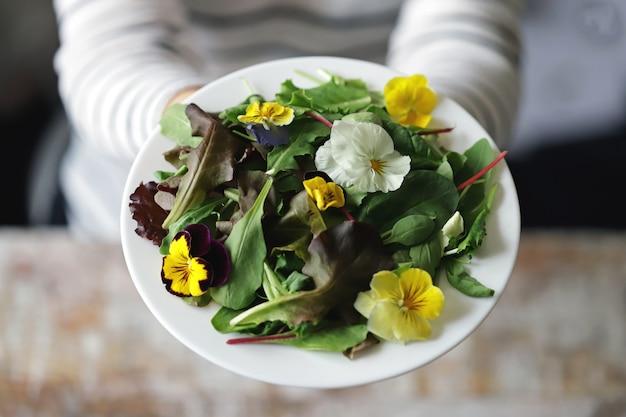 Mischung von salaten mit blumen auf einem weißen teller, der von einem mädchen gehalten wird