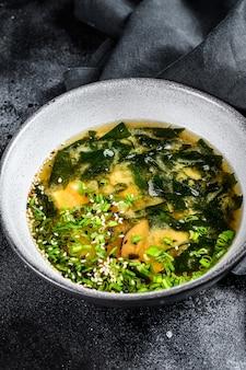 Misosuppe mit tofu und seetang. schwarzer hintergrund. draufsicht
