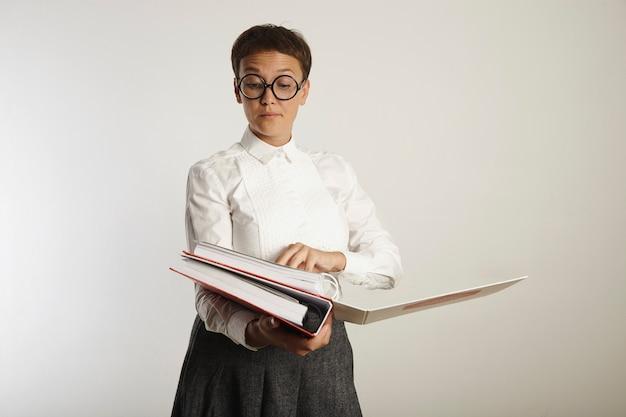 Missbilligende lehrerin mit weißer bluse, grauem tweedrock und brille, die papiere in schweren, auf weiß isolierten ordnern bewertet