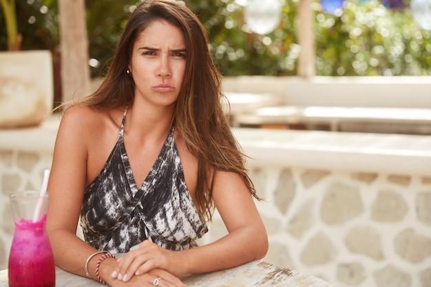 Missbrauchte weibliche models, die mit dem service im terrassencafé unzufrieden sind, schmollen über die lippen, genervt sind, lange auf die bestellung zu warten, umgeben von einem cocktail. unzufriedene touristin ruht im heißen land