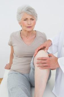 Missfallene ältere frau, die ihr knie überprüft erhält