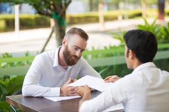 Missfallene bärtige Geschäftsmannsitzung mit Finanzberater