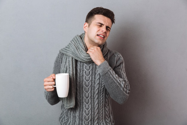 Missfallener krankheitsmann, der den warmen schal hält heißen tee trägt.