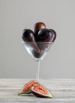 Missionsfeigen in einem martini-glas mit seitenansicht der feigenhälften auf einem holztisch und grauem hintergrund