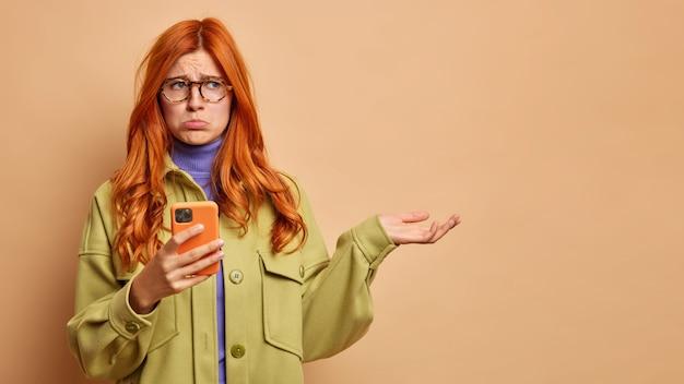 Missmutige unzufriedene rothaarige frau spitzt lippen mit düsterem gesichtsausdruck hält handy und hebt handfläche über leerzeichen kann anwendung nicht herunterladen. technologiekonzept für schlechte emotionen der menschen