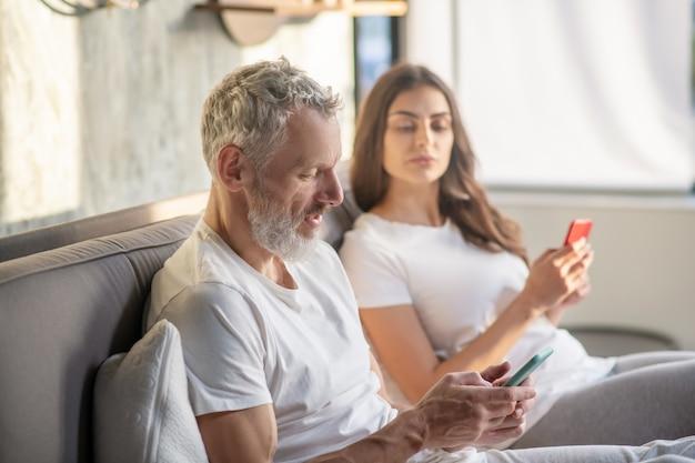 Misstrauen. erwachsener bärtiger ehemann, der auf smartphone starrt und misstrauische frau guckt, die nebeneinander auf bett sitzt