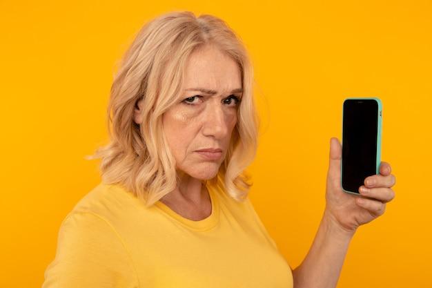 Misstrauen wütende frau mit telefon, das es isoliert im gelben studio benutzt.