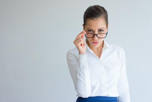 Misstrauische arrogante junge geschäftsfrau, die über ihren gläsern schaut.