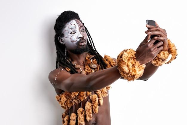 Missverständnis afrikanischen stammes verwenden handy, mit ethnischen gemälden im gesicht, isoliert auf weiß