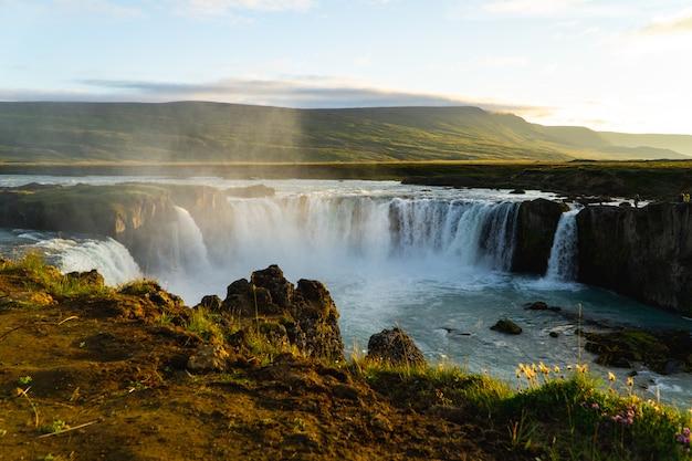 Misty isländischer wasserfall bei sonnenuntergang
