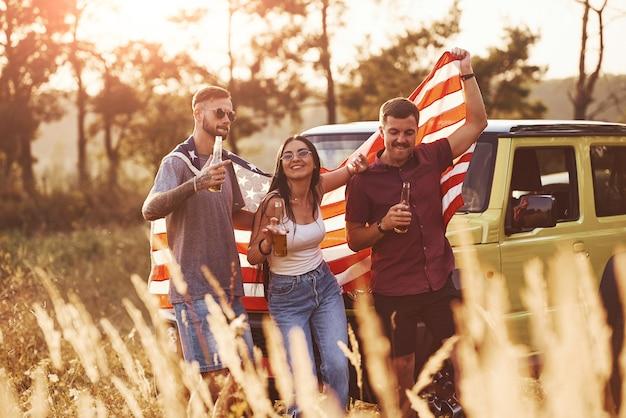 Mit alkohol in den händen. freunde haben ein schönes wochenende im freien in der nähe ihres grünen autos mit usa-flagge.