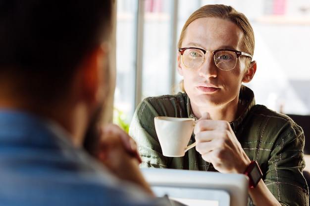 Mit arbeit beschäftigt. ernster blonder mann sitzt seinem kollegen mit kaffee gegenüber, während er zusammenarbeitet