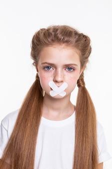 Mit bedeckten mündern. ansprechendes langhaariges kleines mädchen im weißen t-shirt, das wegen des geschlossenen mundes traurig ist