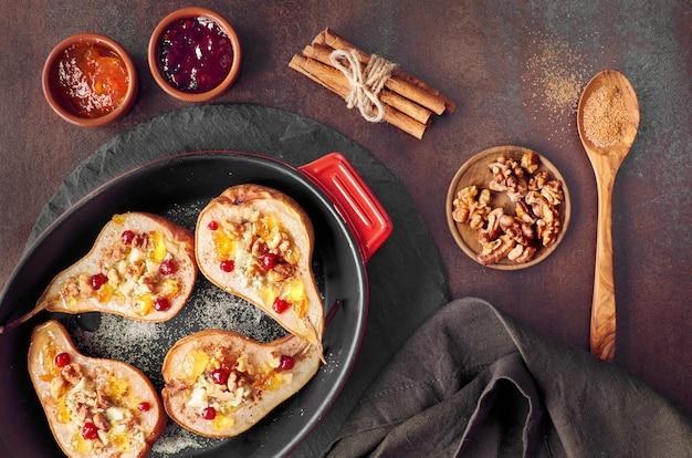 Mit blauschimmelkäse und walnüssen gebackene birnen, serviert mit orangen- und preiselbeermarmelade,