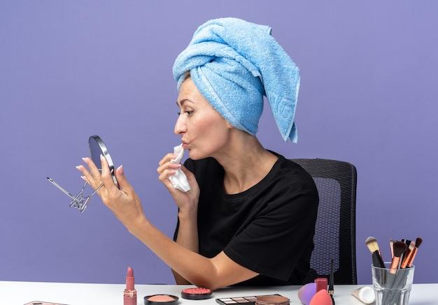 Mit blick auf den spiegel sitzt das junge schöne mädchen am tisch mit make-up-tools und wischt sich die haare im handtuch ab und wischt das gesicht mit serviette isoliert auf blauer wand ab