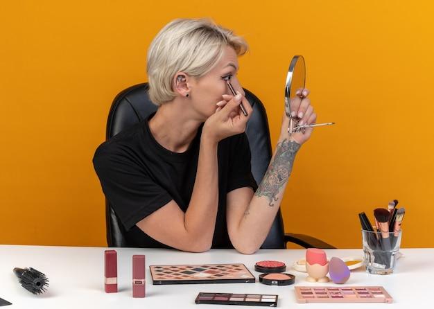 Mit blick auf den spiegel sitzt das junge schöne mädchen am tisch mit make-up-tools und zeichnet pfeil mit eyeliner isoliert auf oranger wand