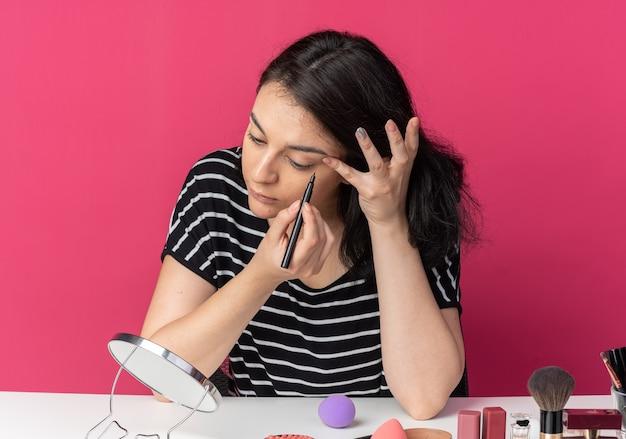 Mit blick auf den spiegel sitzt das junge schöne mädchen am tisch mit make-up-tools