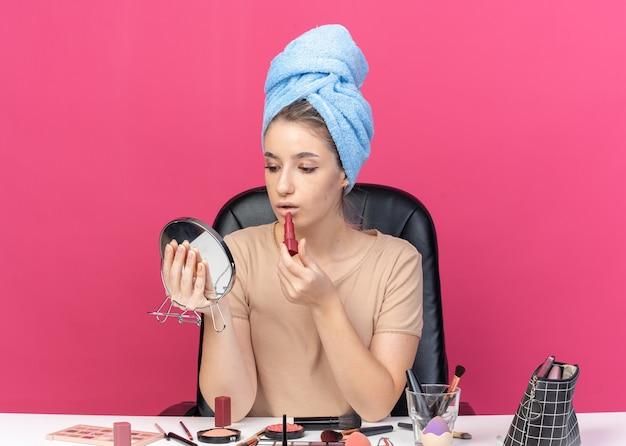 Mit blick auf den spiegel sitzt das junge schöne mädchen am tisch mit make-up-werkzeugen, die haare in ein handtuch wickeln und lippenstift auf rosa wand auftragen
