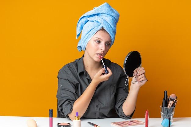 Mit blick auf den spiegel sitzt eine schöne frau am tisch mit make-up-tools, die haare in ein handtuch wickeln und lipgloss auftragen