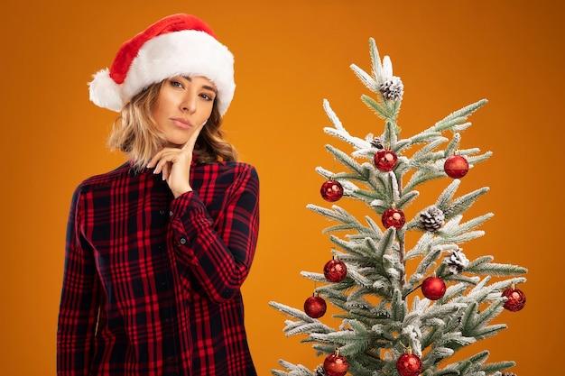 Mit blick auf die kamera, die den kopf neigt, junges schönes mädchen, das in der nähe des weihnachtsbaums steht und einen weihnachtshut trägt, der den finger auf die wange legt, isoliert auf orangem hintergrund