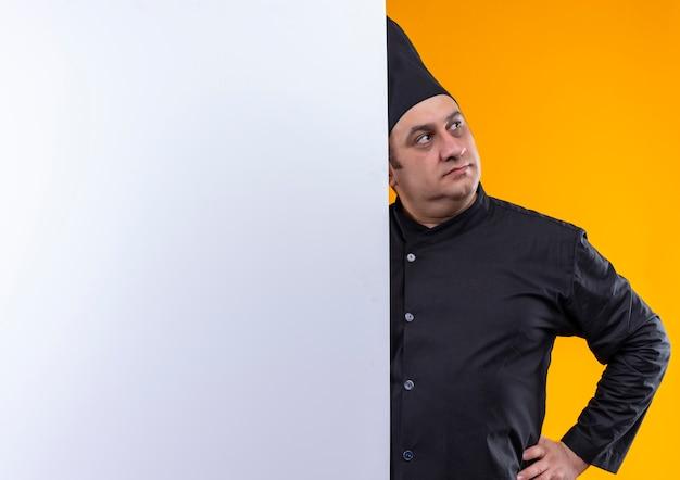 Mit blick auf die seite des männlichen kochs mittleren alters in kochuniform legte er seine hand auf die hüfte und hielt die weiße wand an der gelben wand mit kopierraum